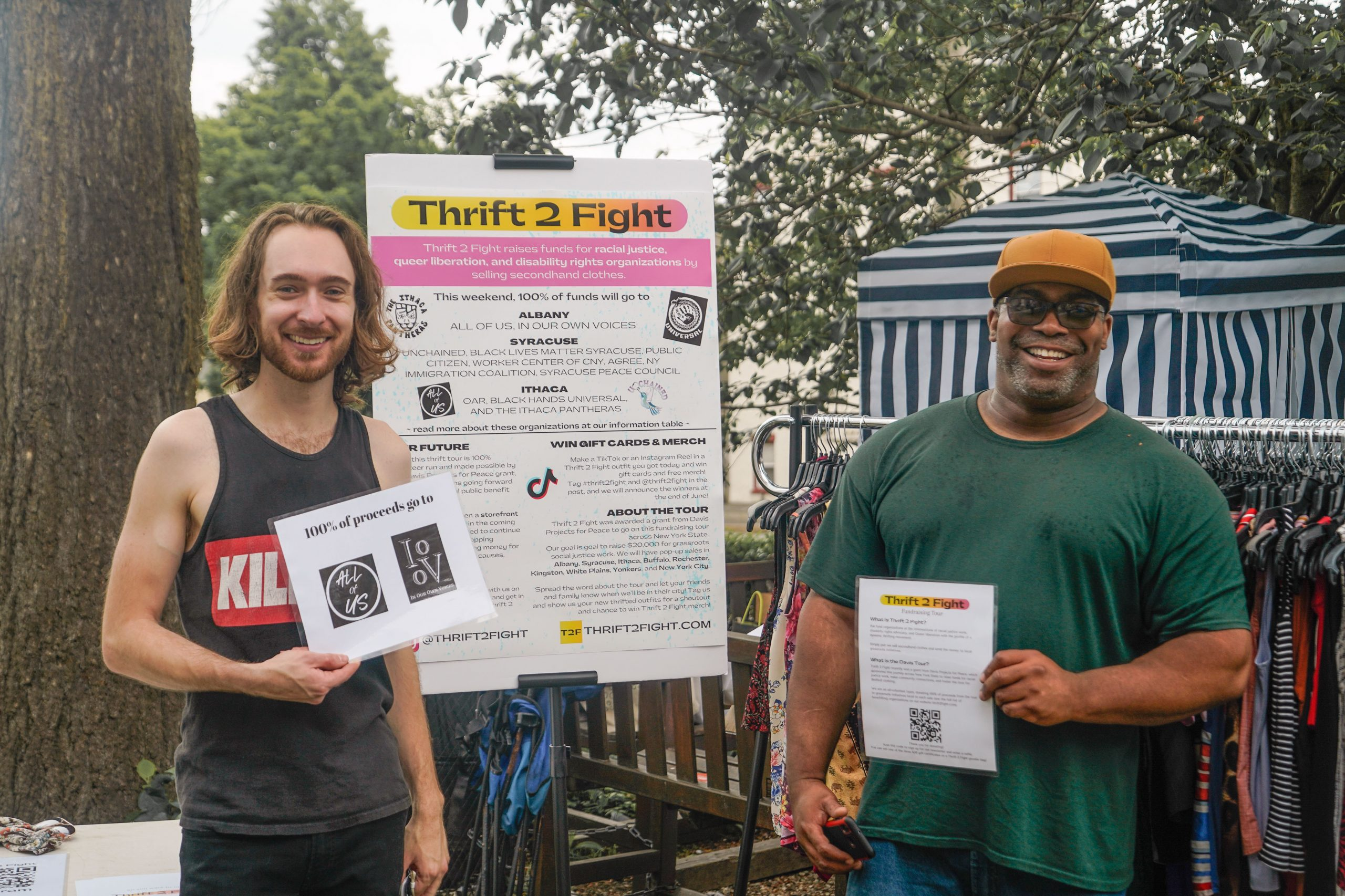 Collin and Gordon are standing next to the Thrift 2 Fight info board at the Albany Tour Sale